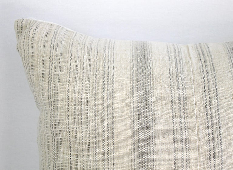 Antique homespun linen and striped grain sack pillow light grey and creamy white striped grain sack front, the backside is finished in a off white natural French linen. The front of the pillows are made from 19th century homespun linen, and the