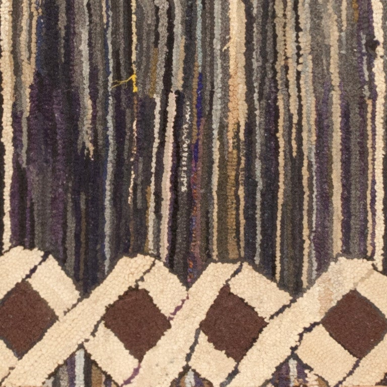 Antique Hooked rug, country of origin: America, date circa early 20th century. Size: 2 ft. 10 in x 3 ft. 9 in (0.86 m x 1.14 m)  This spectacular antique American hooked rug features a grand latticework frame with beautifully executed ribbons that