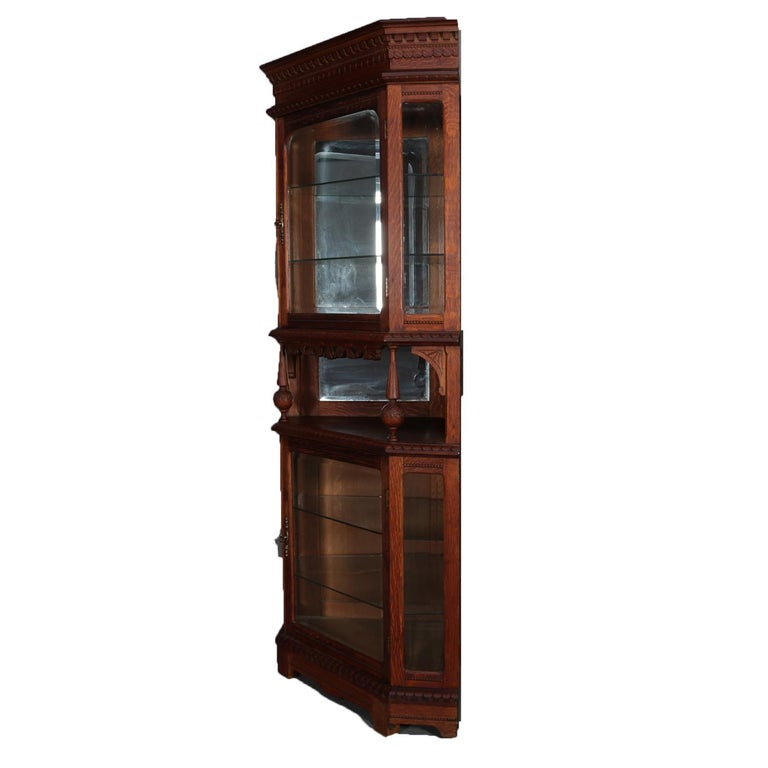 An Antique Horner School Corner Cabinet Features Faceted Form With Oak Construction Having Gl Enclosed Upper