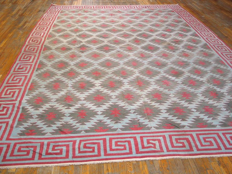 The creamy field displays offset half-drop rows and columns of flattened ashiks with brown details, within a bold bitonal squared wave border which gives a strong sense of movement around this antique Indian all-cotton kilim-woven piece. Good