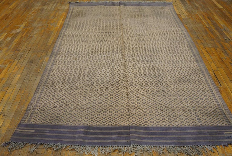 This is a really antique piece since dhurries over 100 years of age are truly rare. And it has a lozenge lattice pattern of weft-float beige yarns on a blue plainweave ground. Banded blue end panels. Striped and dotted side borders. Good condition.