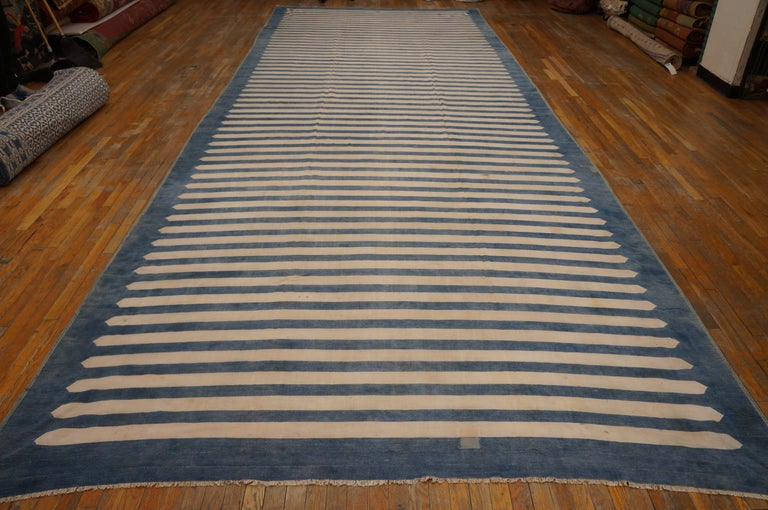 The bitonal horizontal stripe pattern, especially in ecru and light blue is a Dhurrie mainstay, and here the ecru stripes are pointed to neatly fit on the light washed denim blue ground. This vintage all-cotton pileless carpet is in good condition