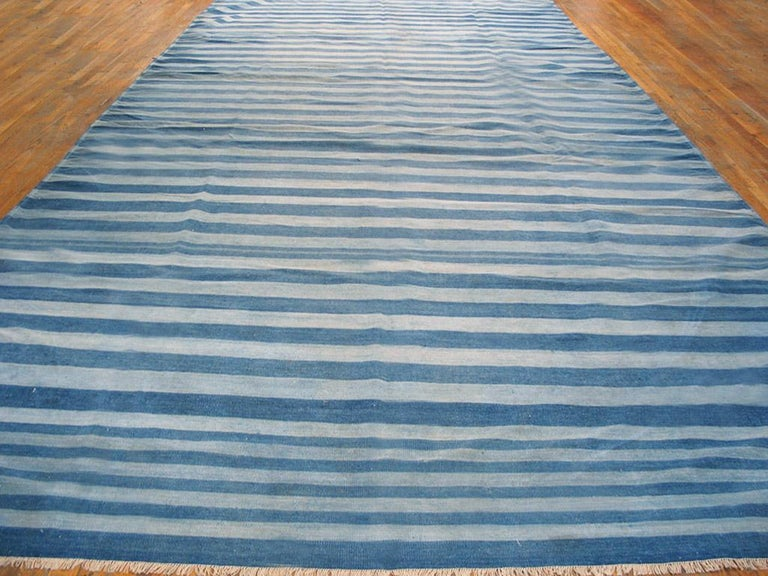 This all-cotton Indian Kilim-weave gallery format Dhurrie has a faintly Caucasian/ NW Persian design air about it with a denim blue field displaying a concentric lozenge over-pattern of serrated ashiks in teal blue, salmon-rust, red and sand, within