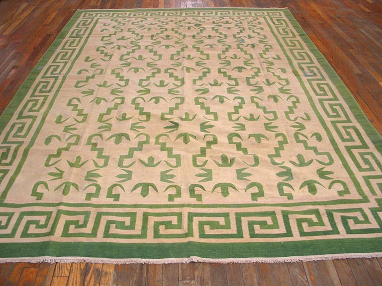 Not all Dhurries have simple stripes, as in this example with a cream cotton field and an allover camel pattern of stepped and hooked squiggles in four columns. Square wave border and corner squares. Works like a pile carpet, but better for the warm