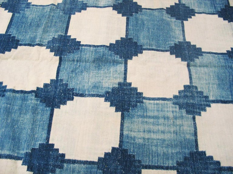 This all cotton tapestry-woven flat dhurrie carpet shows a nine column octagon pattern in ecru, and light and medium denim blue, with a doubled stepped lozenge border. The blues attractively Abrash throughout. Good condition.