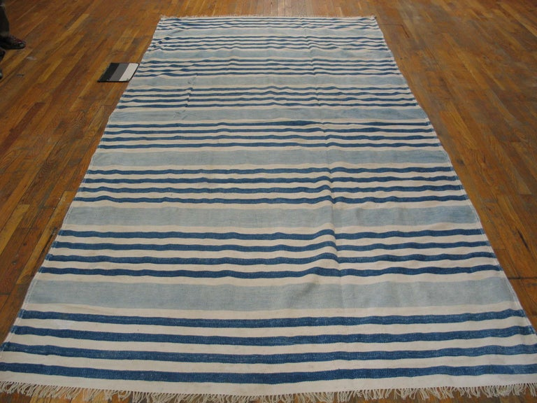Nine bunches of ecru and denim blue lines, all running borderless along the sides, are divided by wide powder blue stripes on this long-rug (kellegi) format all-cotton Indian antique to vintage flat-weave in good condition. Versatile size,