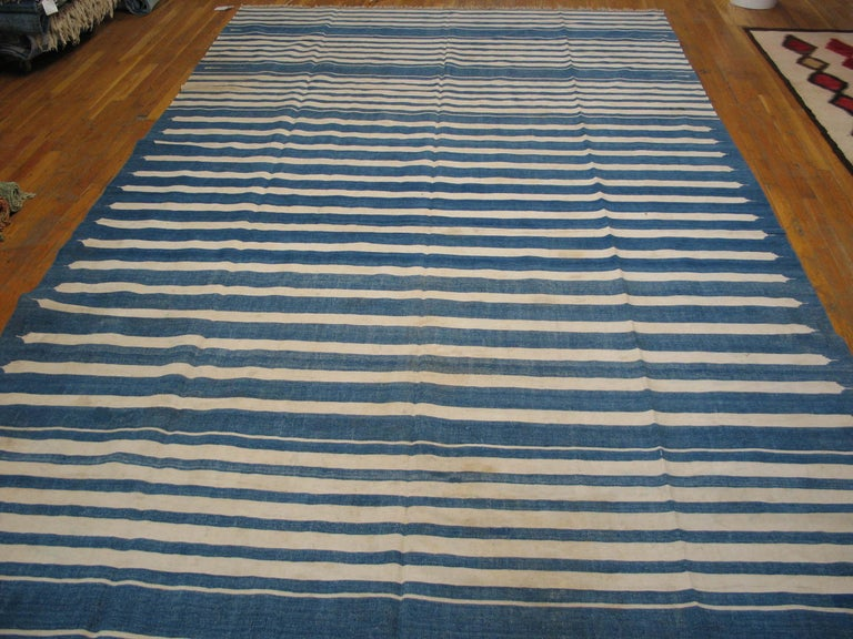 Blue and white is probably the most popular 20th century Dhurrie color combination. Our extensive collection is especially strong on the vintage to antique pieces with full or partial, as here, blue and ecru striped and no lateral borders. The blue