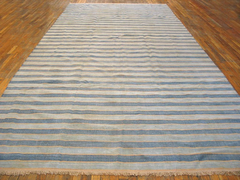 A virtually infinitely size adjustable gallery carpet format Indian bitonal flat-weave with full width stripes in ecru and cleverly abrashing medium blue. With all cotton construction and good condition. Narrowest pale yellow lines add a subtle