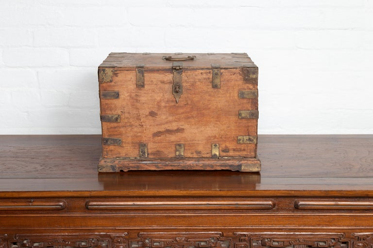 An antique Indian wooden jewelry box from the 19th century, with drop front and six hidden drawers. Born in India during the 19th century, this charming jewelry box features a nicely rustic appearance. Presenting a linear frame accented with brass