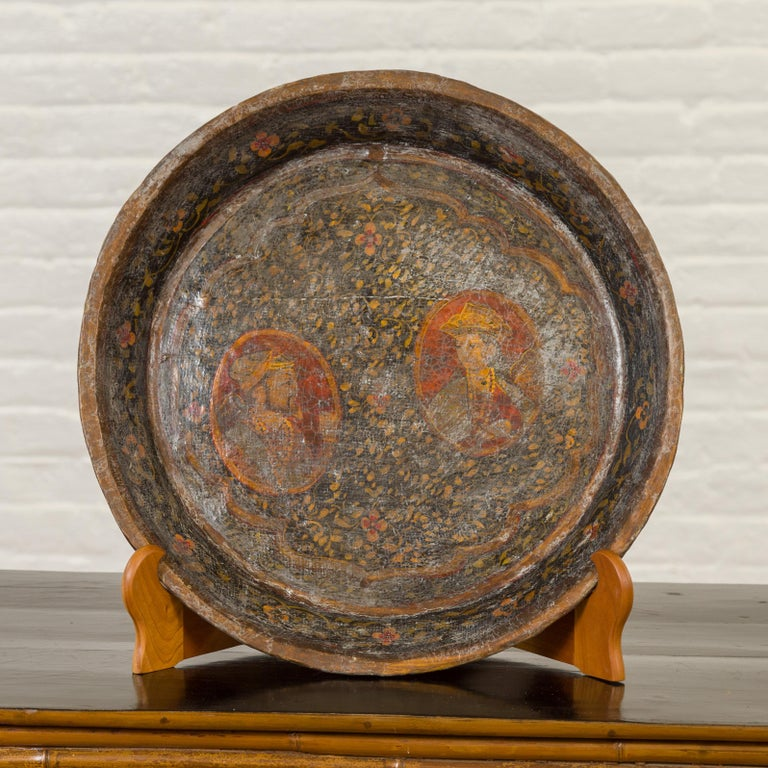 An antique Indian market tray from the 19th century, with Mughal inspired hand painted decor. Created in India, this market tray features a Mughal inspired hand painted decor depicting two portraits each in a medallion and surrounded by abundant
