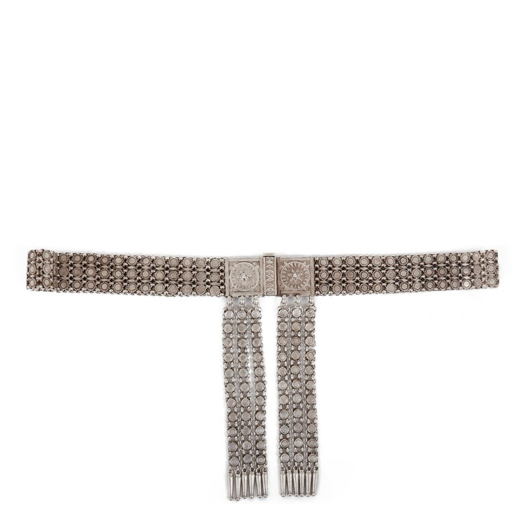 A beautiful and finely made antique Indian silver metal belt with ornate moulded square form buckle held together by a heavy twin pronged pin, the belt with a series of rounded studs set within a chainmail body and with six tassels fastened to and