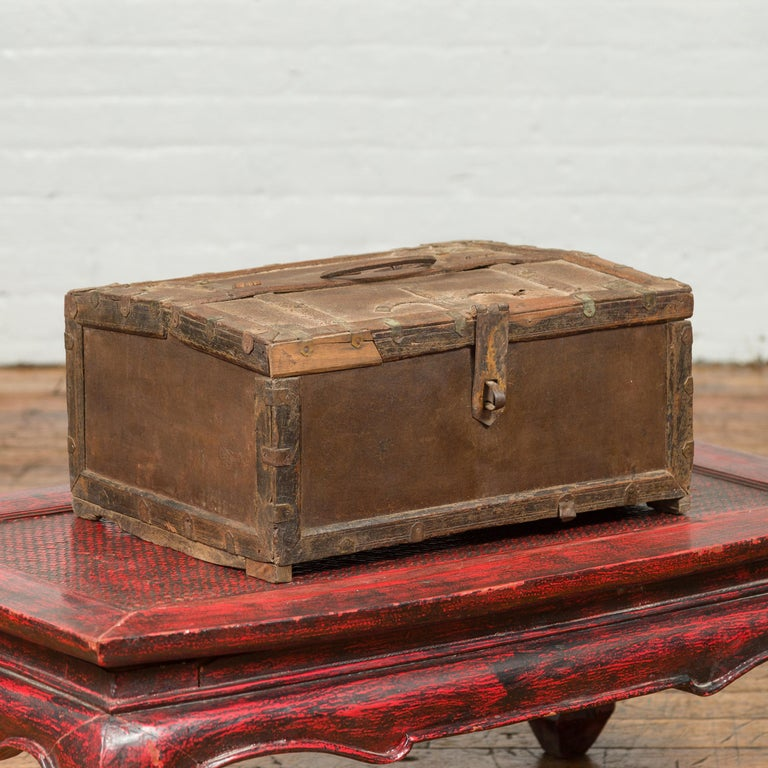 An antique Indian wooden box from the 19th century with iron hardware and weathered appearance. Topped with a rectangular lid half opening to reveal a partitioned interior, this old cash box is raised on petite feet. Boasting a charming air of