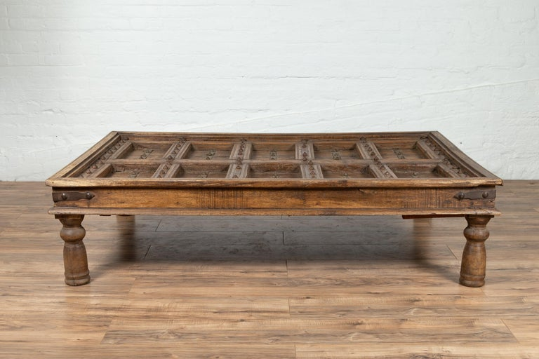 An antique Indian palace wooden door made into a coffee table with iron accents and baluster legs. Born in India during the early years of the 20th century, this exquisite palace door has been made into a coffee table. The top is rhythmically
