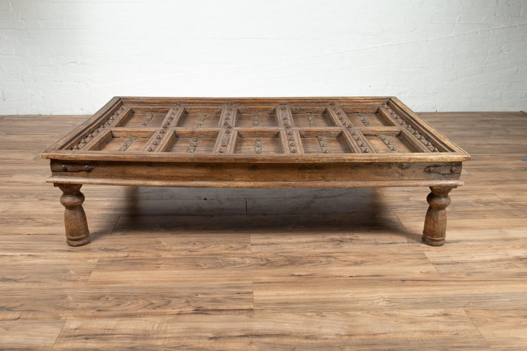 Turned Antique Indian Wooden Palace Door Made into a Coffee Table with Iron Braces For Sale
