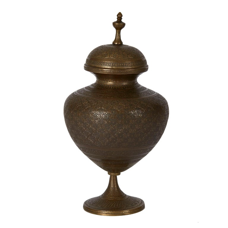 An impressive antique Indo-Persian bronze lidded pedestal vase, the bulbous body extensively decorated with finely engraved patterning and fitted with a domed cover with raised finial and supported on a narrow pedestal base on a rounded and slightly