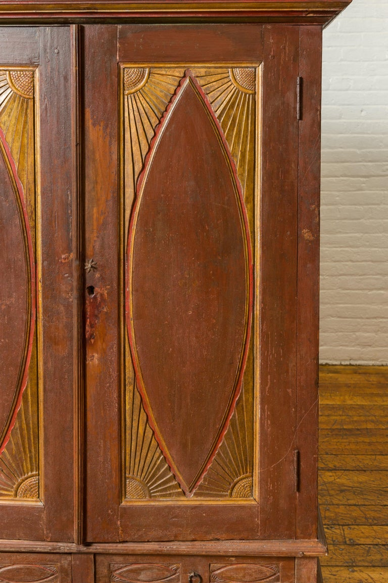 Wood Antique Indonesian Cabinet with Carved Almond Style and Sun Ray Motifs For Sale