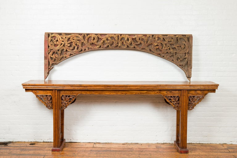 An antique Indonesian carved and painted architectural panel from the 19th century, with rinceaux motifs. Crafted in Indonesia during the 19th century, this architectural fragment attracts our attention with its traces of red and gold polychromy,