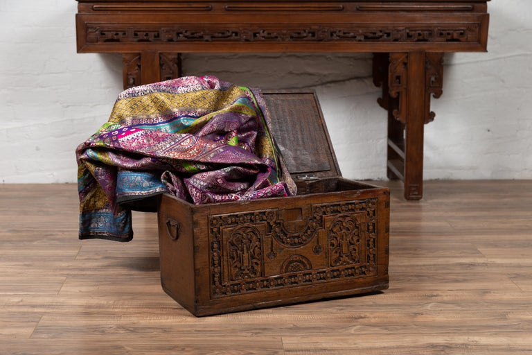 An antique Indonesian decorative wooden box from the early 20th century, with carved front. Born in Indonesia during the early years of the 20th century, this charming wooden box features a clean silhouette. The rectangular lid opens to reveal a