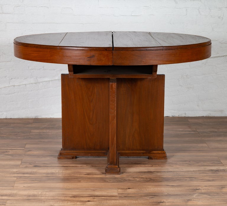 An antique Indonesian wooden dining table from the early 20th century, with central folding leaf and geometric base. Born in Indonesia during the early years of the 20th century, this stylish dining table features a circular planked top concealing a