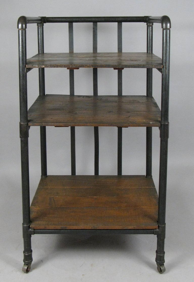 A very handsome 1950s rolling industrial cart or bookcase, with a cast iron frame and dark walnut stained shelves. Mounted on its original casters.