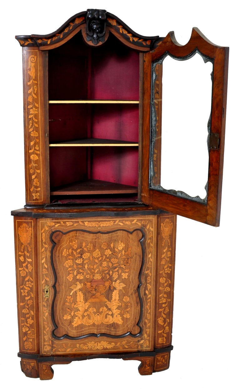 Antique inlaid marquetry Dutch two-piece corner cabinet, circa 1830. The cabinet with an arched top with a carved floral finial to the center, the top section having a single door enclosing two shelves, the base also having a single door enclosing