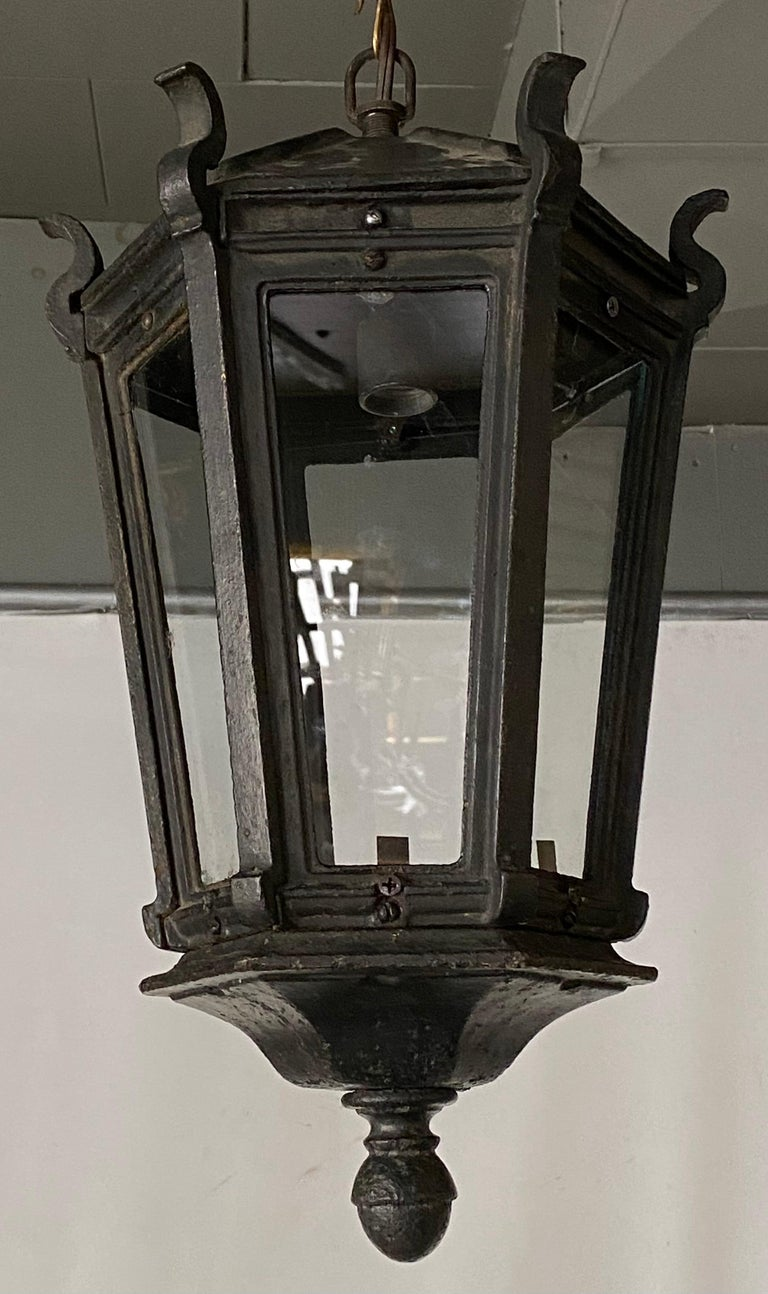 Handsome and impressive iron ceiling hanging lantern with great aged patina for either interior or exterior lighting. The shaped crown top leads down to a hexagonal body with glass panels. Chandelier, pendant light, hanging lantern.