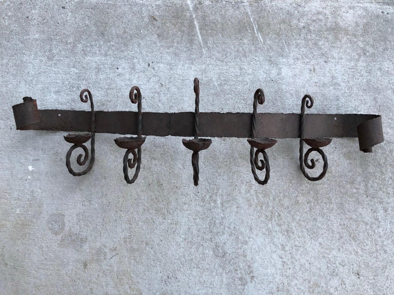 Antique iron wall sconce. Perfect for above a mantel or bed / headboard. Holds 5 candles. All handwrought with rolled scroll like ends and twisted candle holders. Rustic style perfect for that stucco style hacienda. Arched back. Attaches to wall on