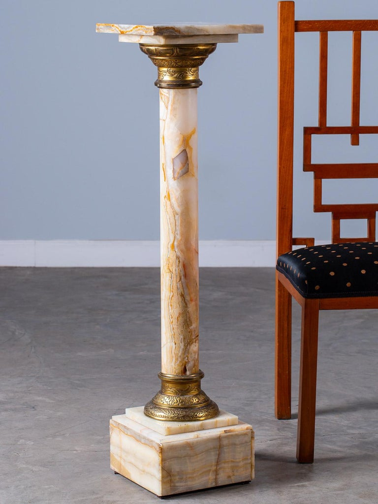 Antique Italian alabaster column pedestal with etched gilt bronze collars, circa 1890. This Classical style pedestal column is taken from examples seen in the ancient civilizations of Greece and Rome. Having a removable display top the slender