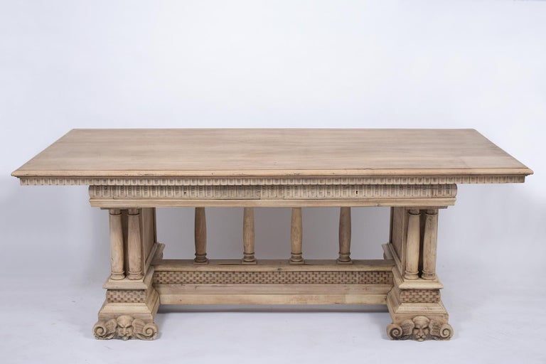 This antique Italian Baroque style dining room table is made out of walnut wood with a newly bleached finish and has been completely restored. This dining table features a large wooden top, detailed carved moldings throughout, and two large top