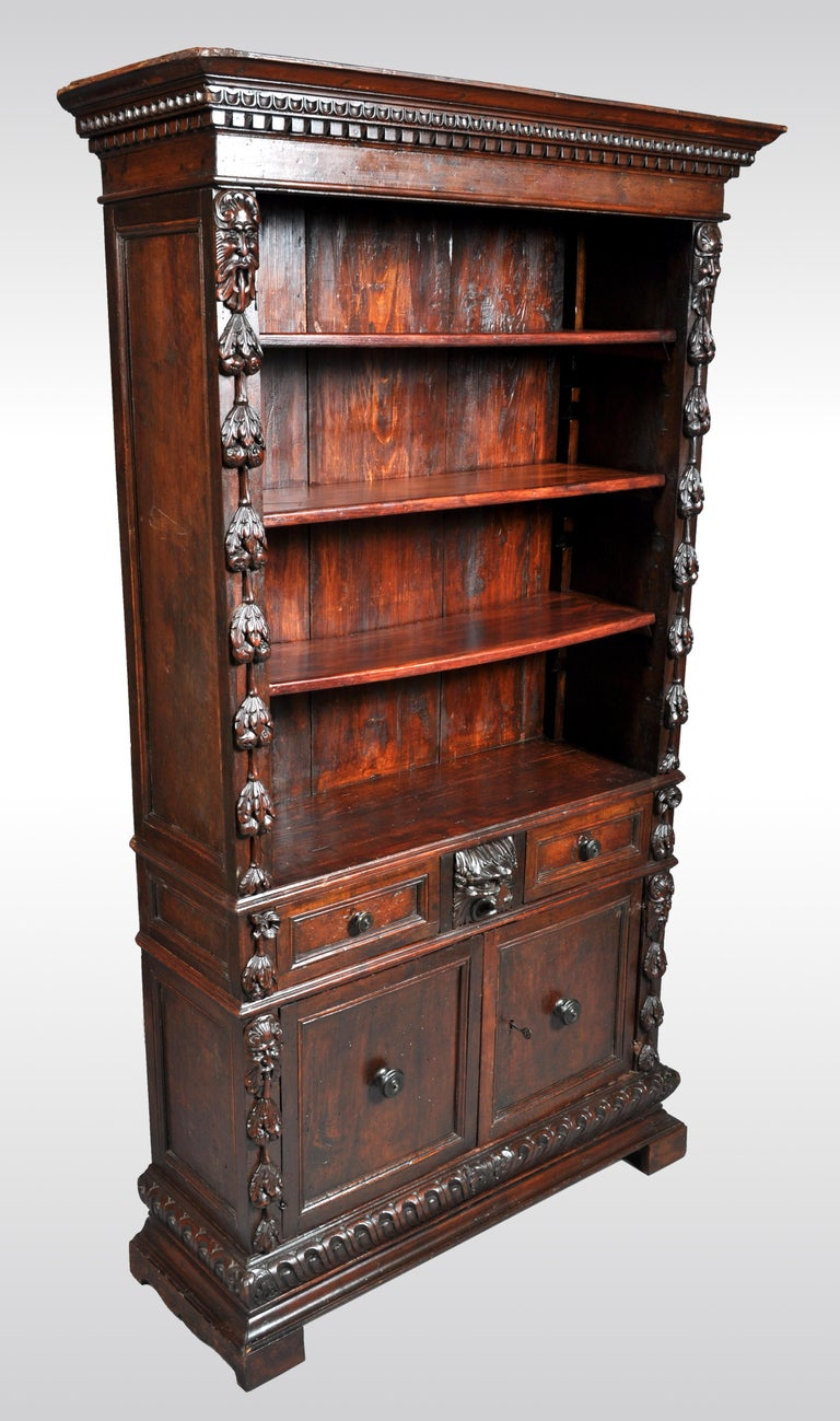 Antique Italian carved walnut renaissance revival bookcase, circa 1870. The bookcase having a protruding cornice with 'egg and dart' and dentil carving, the bookcase is flanked with carved fruits preceded by comical grotesque masks. The base having