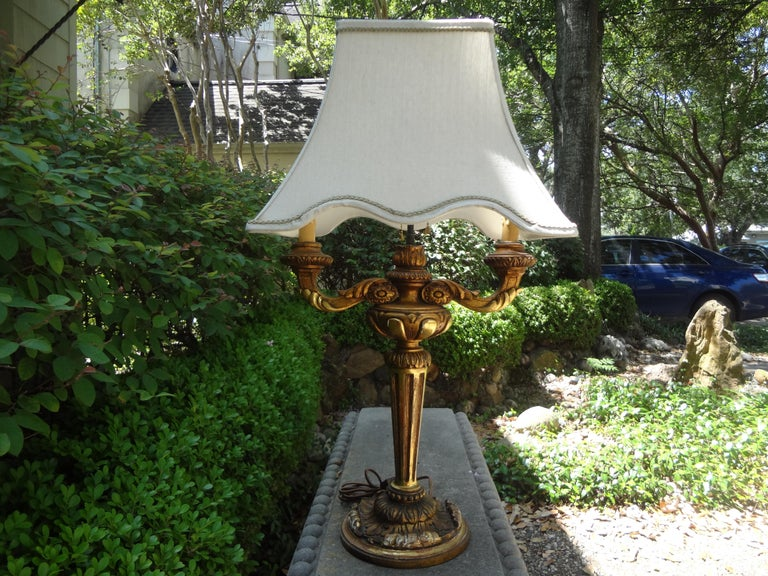 Stunning antique Italian gilt wood lamp. This lovely Italian gilt lamp has been newly wired to U.S. specifications. Gorgeous patina! Dimensions of lamp only: 28 inches high 8 inches diameter of base.
