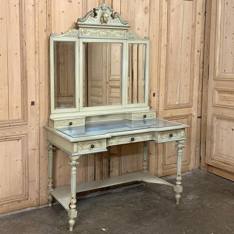 Antique Italian Louis XVI painted vanity features a strong carved crown overlooking the tripanel folding mirror below, which in turn rests atop a pair of drawers and cubby hole, and again which rests upon the main glass topped surface. Carved floral