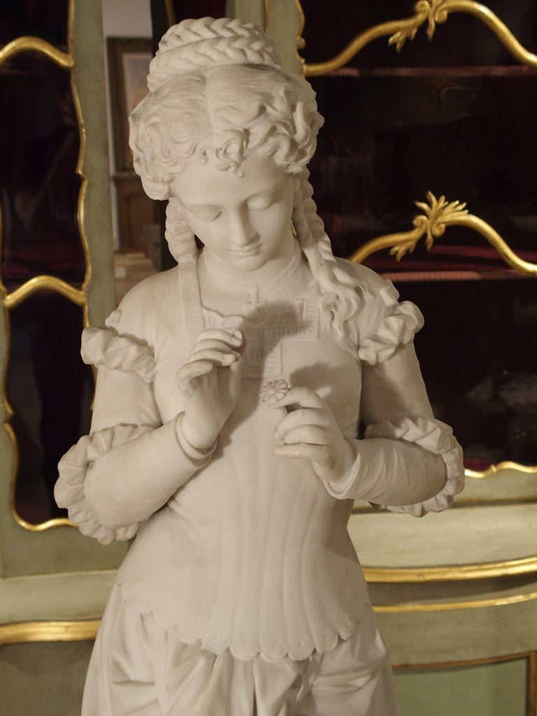 This beautiful marble statue of a young woman holding a single flower dates to the 19th century and is of the Italian school. She is shown wearing a long, dropped waist dress that is slightly hiked up by her purse. The back of the dress is cross
