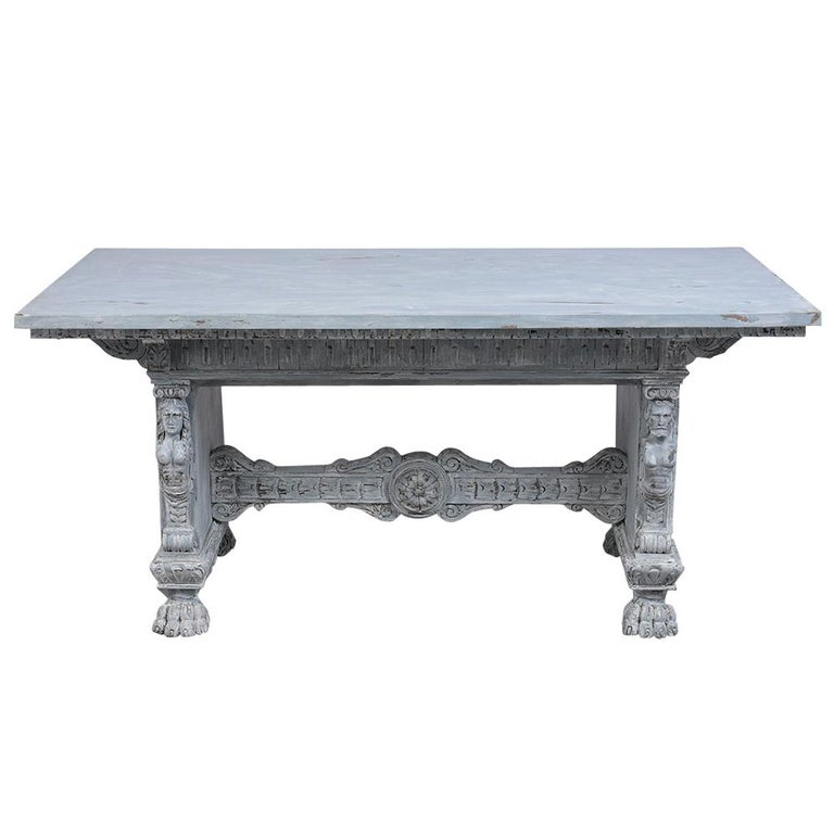 This antique Italian Renaissance dining room table is made out of walnut wood and newly painted a pale gray and off white color with a distressed finish. This dining table features a wooden top with detailed moldings and heavily carved wood accents