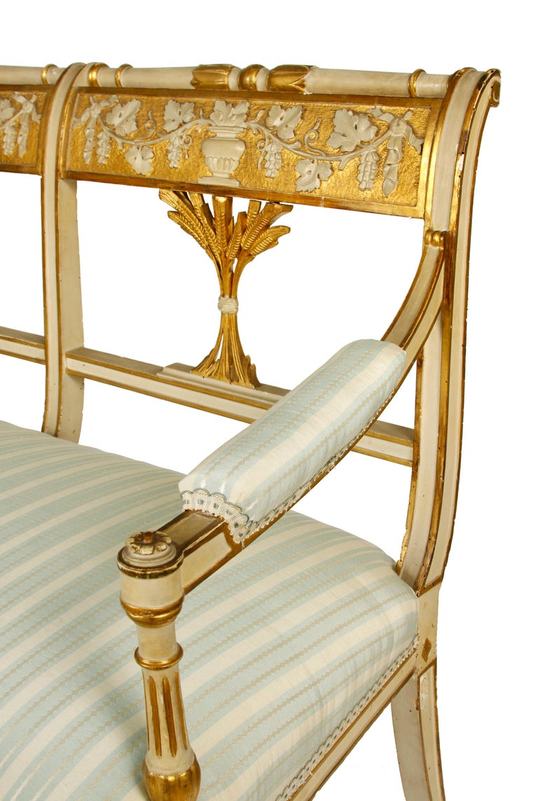 Antique Italian painted and gilt settee. Louis XVI style circa 1900 with carved back depicting wheat, grapes and vines. Newly reupholstered in blue and cream striped fabric.