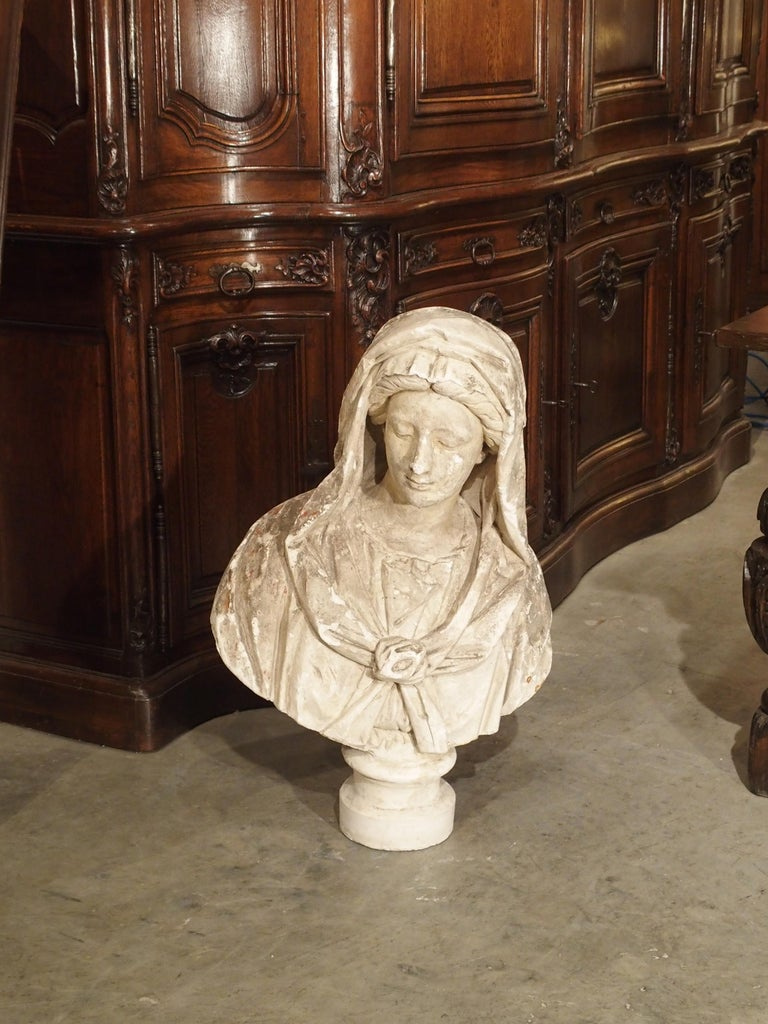 This serene Italian plaster bust of a woman dates to circa 1890. She is gazing downward and slightly to her right. The draping of the fabric, the tied bow on her chest, and details of her facial features are all very well done. The patina of this
