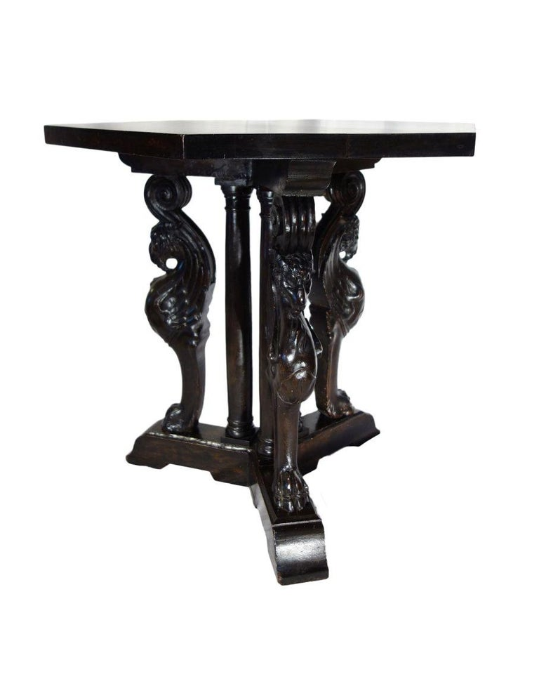 Striking Renaissance Revival period figural carved triple pedestal occasional table featuring Griffons - the legendary mythological hybrid of Eagle & Lion. Relative to the Egyptian Sphinx, the Griffon has been depicted in Europe in Roman bronzes of