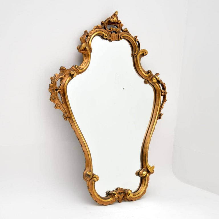 A stunning vintage gilt wood mirror in the antique Italian style. This dates from around the 1950's.  It is well made and has a beautiful design. There is some minor wear to the frame and some very small areas of distress to the silvered backing