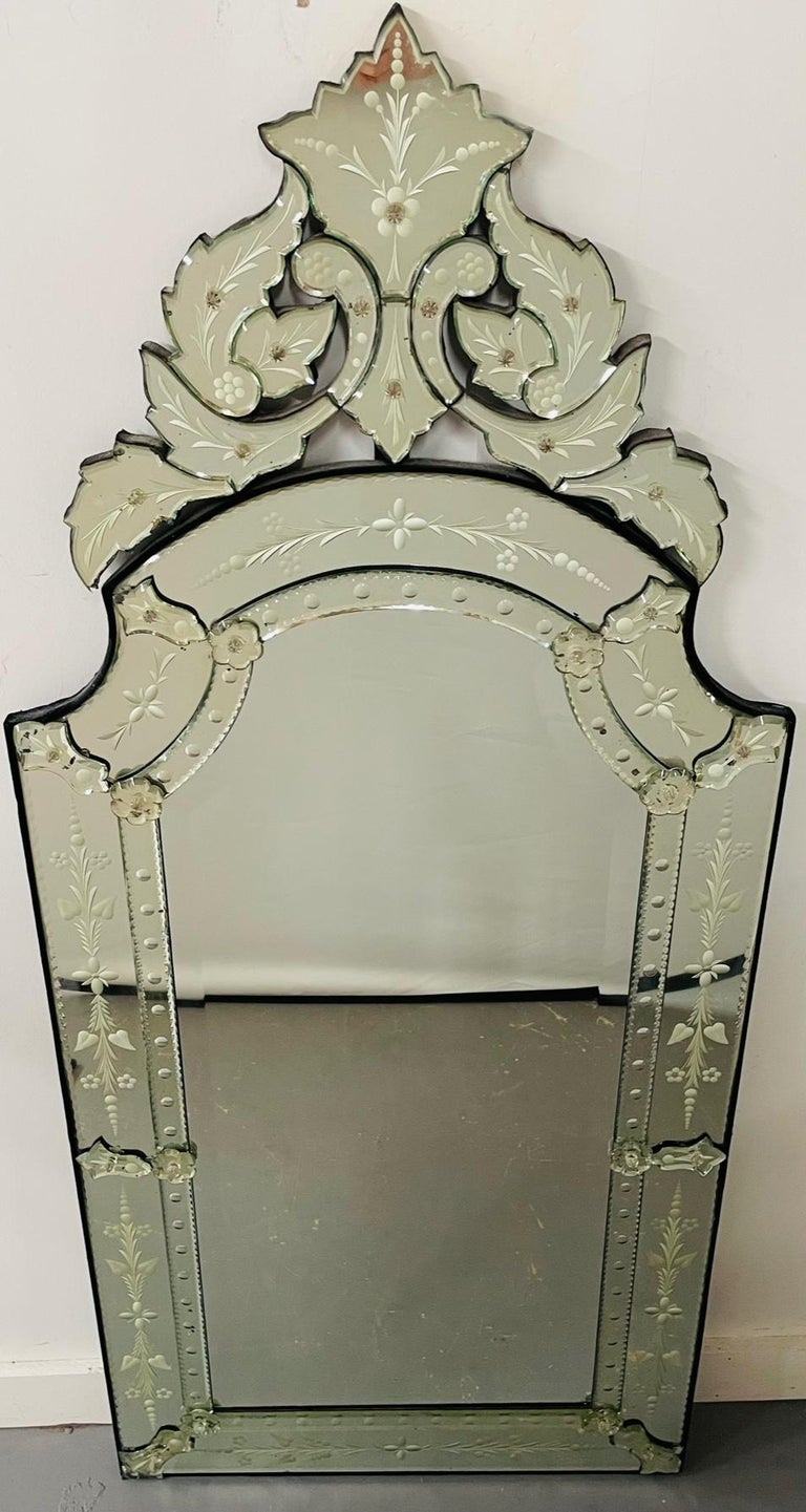 An exceptional antique Venetian etched glass wall mirror. The Venetian mirror features beautiful acanthus and floral etching design. The crown of the mirror is finely designed in acanthus pieces, adding style and elegance to this refined wall piece.