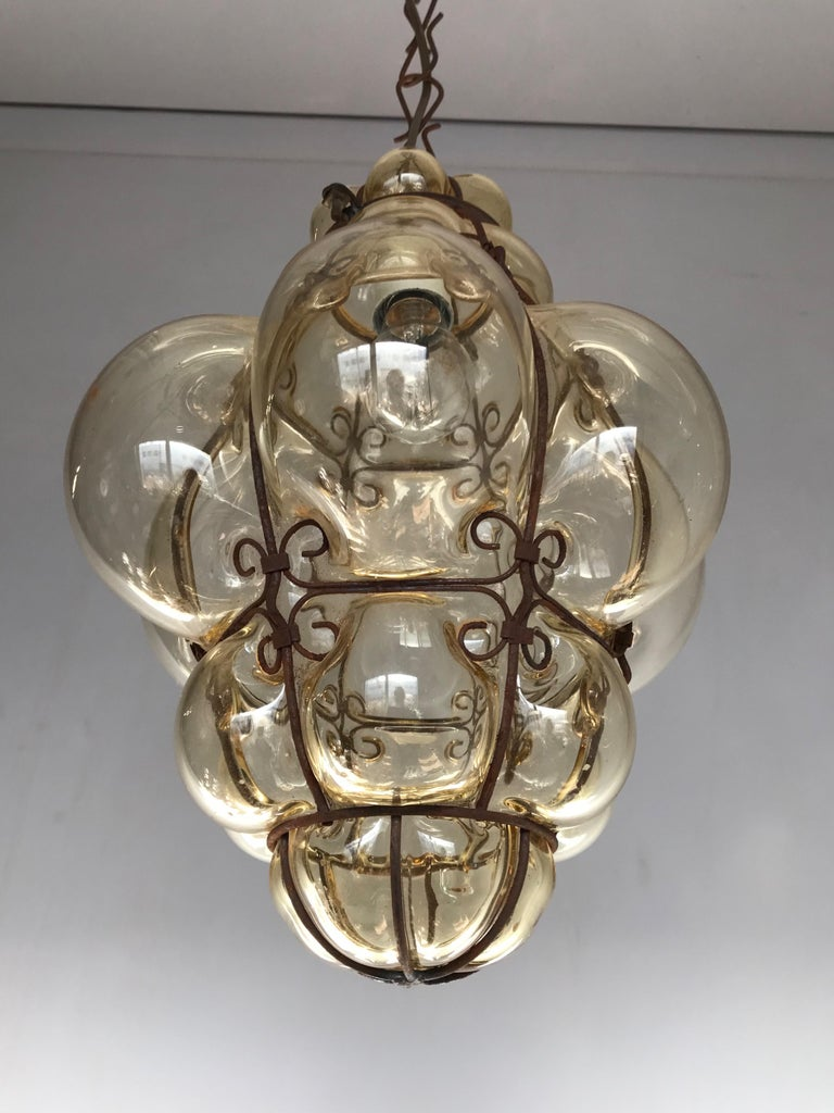 Beautiful color and practical size fixture with mouthblown glass in a metal frame.  If you are looking for a rare and stylish fixture to grace your home then this handmade antique specimen could be perfect. With early 20th century lighting as one