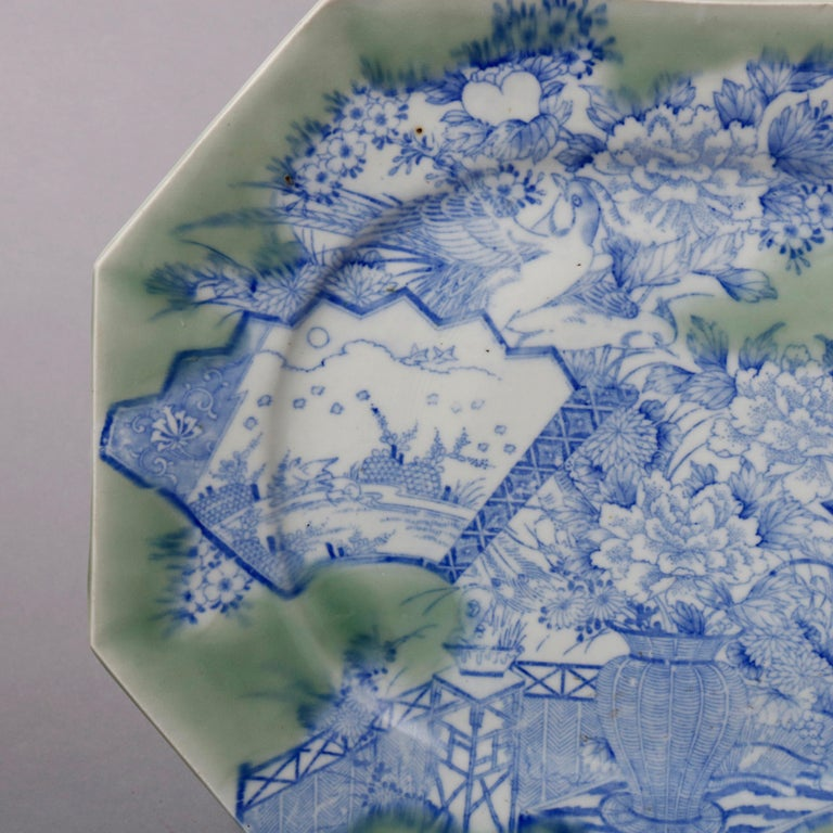 An antique Japanese Aesthetic Movement porcelain platter offers elongated octagonal form with blue and white scenic and floral all-over decoration against celadon green ground, having faceted rim with en verso blue decoration, 19th