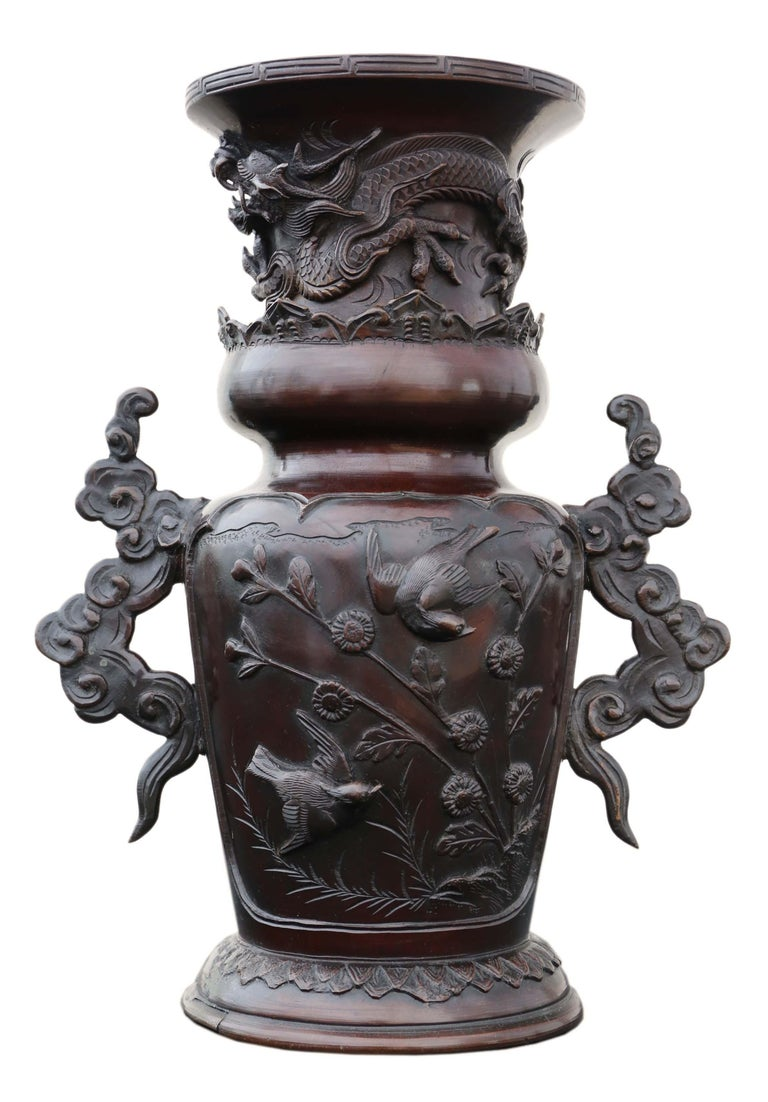 Early Japanese Meiji period bronze vase. Raised dragon with birds and cloud handles.