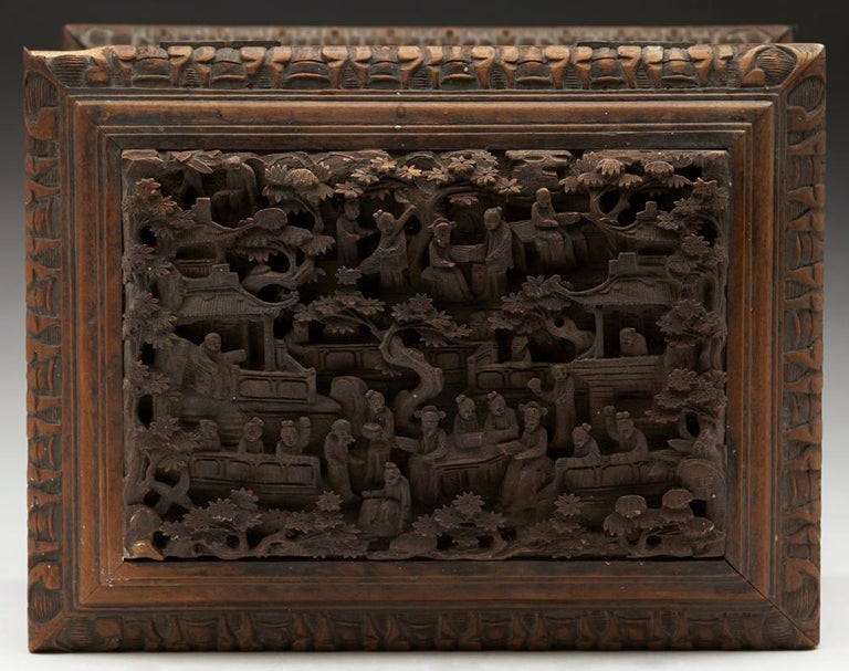 An antique Chinese Canton Qing wooden jewelry box carved in high relief with figural panels and dating from the 19th century. This stunning box of rectangular casket shape stands on a pedestal shaped base with a carved edge and has relief carved