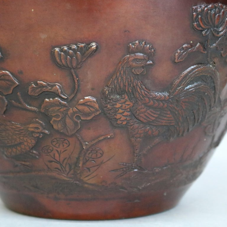 An antique Japanese jardinière offers bronze construction having embossed garden scene with birds and flowers, circa 1920.  ***DELIVERY NOTICE – Due to COVID-19 we are employing NO-CONTACT PRACTICES in the transfer of purchased items.  Additionally,