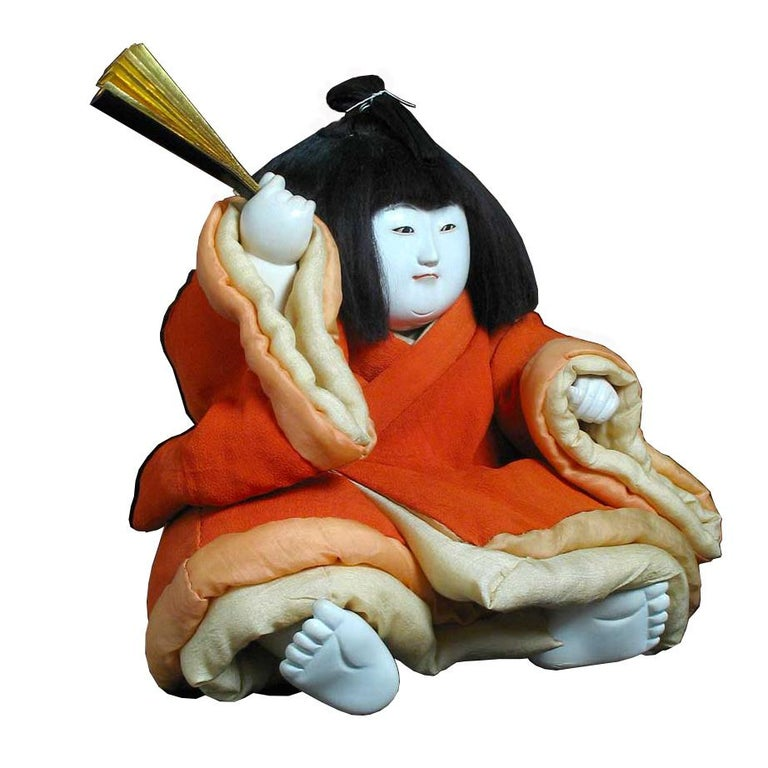 Japanese Gosho Ningyo, a palace figure of a young noble boy seated with his feet extended forward holding a gold leafed folding signal battle fan in his right hand above his head (a symbolic wish for strength and leadership), costumed in a orange