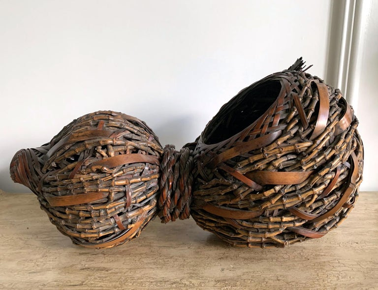 A lovely Japanese bamboo ikebana basket in the shape of gourd with an open mouth and a body circa 1920s-1940s. The piece was woven in great details and styles with mostly irregular and loose twining weaving technique. Several different kinds of