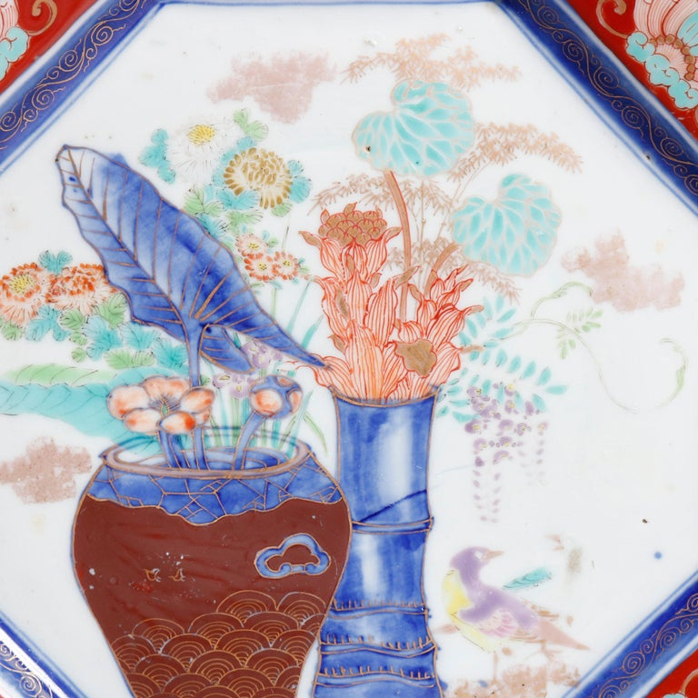 An antique Japanese porcelain charger offers octagonal form with central garden urn scene and faceted border with dragon and foliate reserves, gilt highlights throughout, en verso chop mark signed with blue decoration on rim, circa 1900  ***DELIVERY