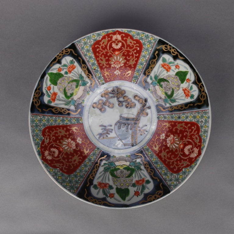 An antique Japanese Imari porcelain charger features hand painted panels of alternating garden scenes and scroll and foliate decoration surrounding central medallion with urn, gilt highlights throughout, en verso decoration, circa 1900.  ***DELIVERY