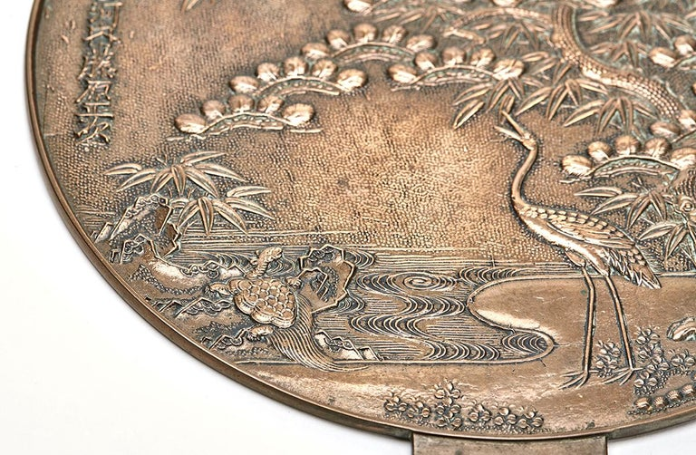 An exceptional and stunning Japanese bronze handled mirror within a fitted black lacquered case. The mirror is polished to one side with the other side moulded in relief with wading birds and a turtle on a shore with a large fruiting tree. The