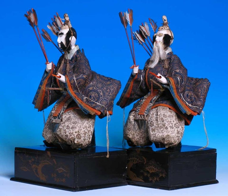 Japanese Takeda Hina Ningyo, of a pair of seated ministers for the Girl's day display, each costumed in matching brocades characteristics the house of Takeda, supported on lacquered and gold painted box bases, each with swords, arrows and bow, the